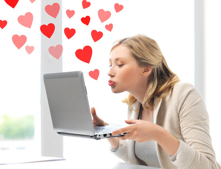 dating: virtual relationships, online dating and social networking concept - woman sending kisses with laptop computer