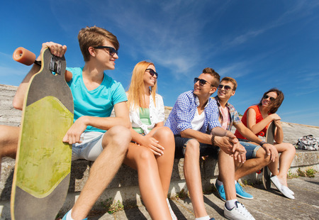 friendship, leisure, summer and people concept - group of smiling friends with skateboards sitting on city street