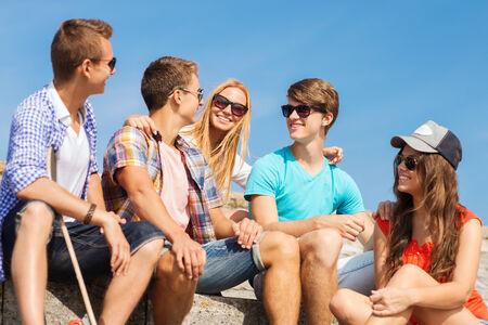 vriendschap, vrije tijd, zomer en mensen concept - groep van lachende vrienden met skateboard zitten op straat stad