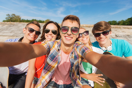 group of young people: friendship, leisure, summer, technology and people concept - group of smiling friends with skateboard making selfie outdoors Stock Photo