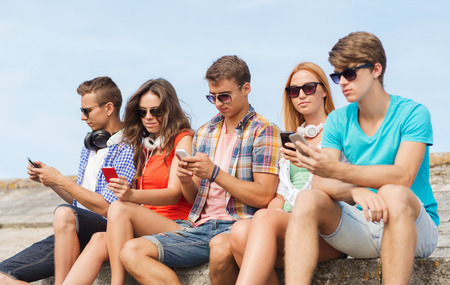friendship, summer, technology and people concept - group of friends with smartphones and headphones outdoors photo