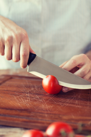 knife tomato: cooking and home concept - close up of male hand cutting tomato on cutting board with sharp knife