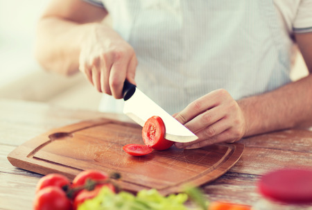 chopping: cooking and home concept - close up of male hand cutting tomato on cutting board with sharp knife