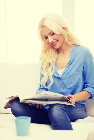 leasure: home and leasure concept - smiling woman sitting on couch and reading magazine at home