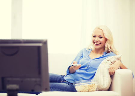 watching movie: food, happiness and people concept - smiling young girl with popcorn watching movie at home Stock Photo