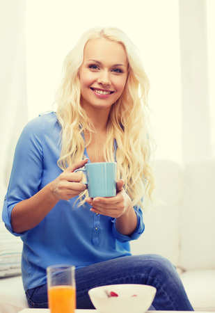 having breakfast: healthcare, food, home and happiness concept - smiling woman with cup of tea, glass of juice and bowl of muesli having breakfast