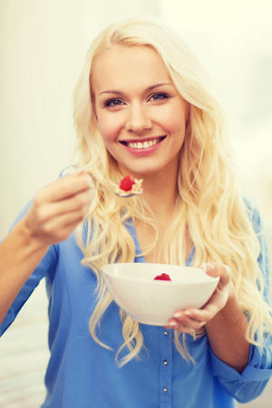 porridge: healthcare, food, home and happiness concept - smiling woman with bowl of muesli having breakfast at home Stock Photo