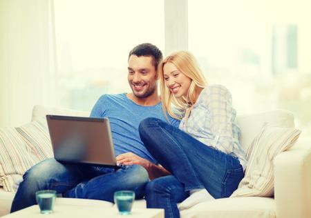 parejas jovenes: amor, la familia, la tecnolog�a, internet y concepto de la felicidad - sonriente feliz ordenador port�til Pareja WITL en casa Foto de archivo
