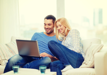 couple on couch: love, family, technology, internet and happiness concept - smiling happy couple witl laptop computer at home