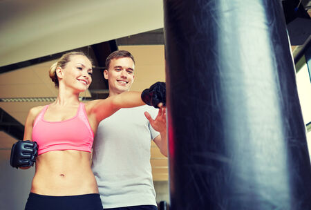 sport, fitness, lifestyle and people concept - smiling woman with personal trainer boxing punching bag in gym photo