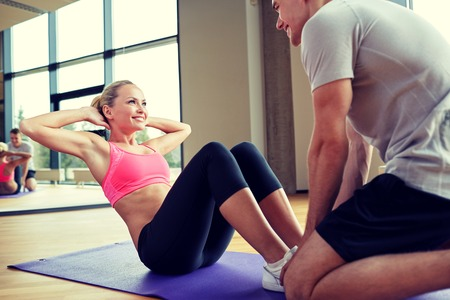 gym: fitness, deporte, entrenamiento, gimnasio y estilo de vida concepto - mujer con entrenador personal haciendo sentadillas en el gimnasio Foto de archivo