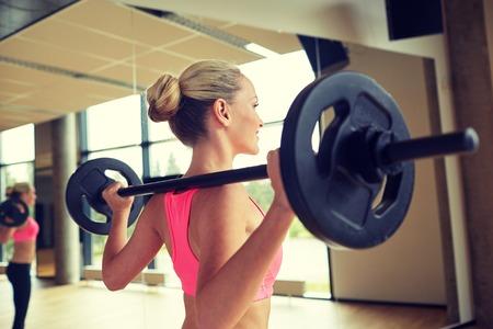 фитнес: фитнес, спорт, пауэрлифтинг и люди концепции - спортивный женщина, осуществляющих с штангой в тренажерном зале