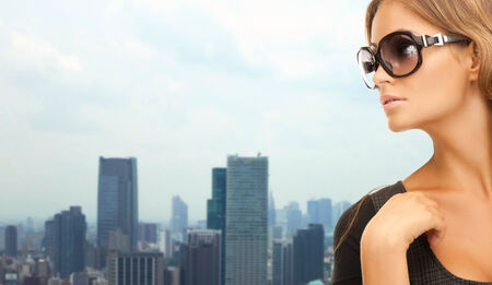 eyewear: people, fashion, eyewear and style concept - beautiful woman in shades over city background