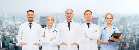 healthcare, people and medicine concept - group of doctors with stethoscopes and clipboard over city background photo