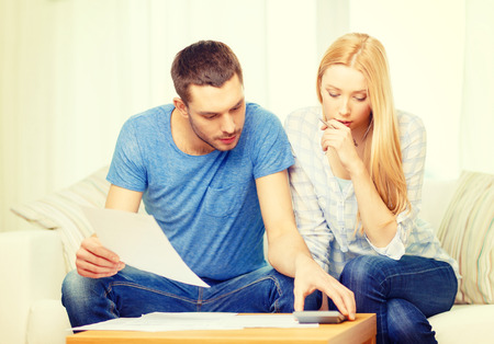 tax, finances, family, home and happiness concept - busy couple with papers and calculator at home photo