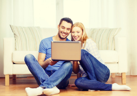 love, family, technology, internet and happiness concept - smiling happy couple with laptop computer sitting on the floor at home photo