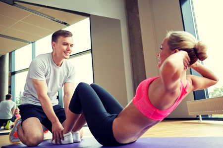 woman working out: fitness, sport, training, gym and lifestyle concept - woman with personal trainer doing sit ups in gym
