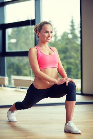 fitness, sport, training, gym and lifestyle concept - smiling woman stretching leg in gym Reklamní fotografie