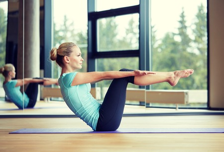 fitness: fitness, deporte, formación y concepto de la gente - sonriente mujer haciendo ejercicios abdominales sobre colchoneta en el gimnasio Foto de archivo