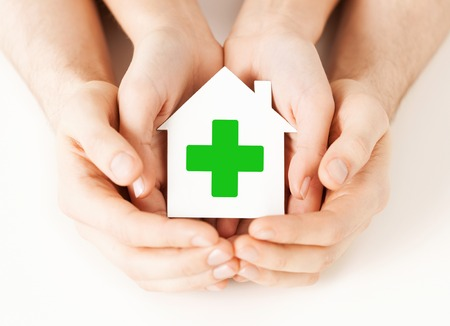cross with care: care, help, charity and people concept - close up of hands holding white paper house with green cross sign