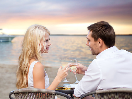 romans: letnie wakacje, ludzie, romans, podróży i randki koncepcja - para picia wina w kawiarni na plaży o zachodzie słońca Zdjęcie Seryjne