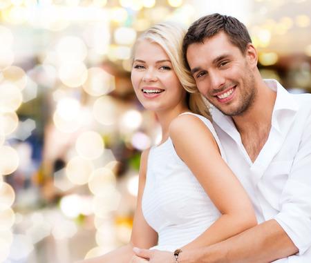 parejas felices: vacaciones de verano, vacaciones, citas, amor y concepto de la gente - feliz pareja se divierte sobre luces de fondo amarillo Foto de archivo