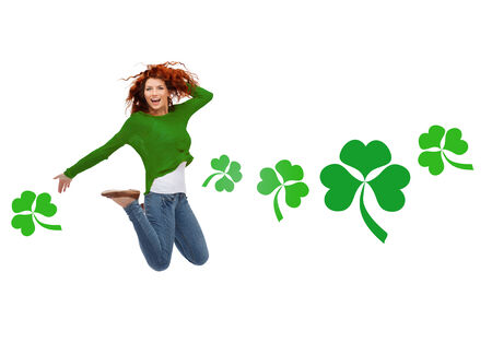 shamrock: motion, happiness, st. patricks day and people concept - happy teenager girl jumping in air over white background with green shamrock or clover