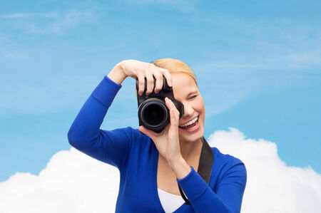 photography, technology, summer and people concept - smiling young woman taking picture with digital camera over blue sky and cloud background photo