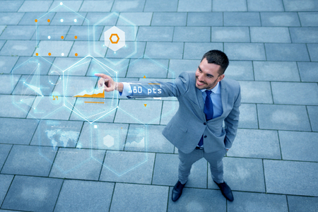 people development: business, development, technology and people concept - young smiling businessman pointing finger to virtual screens with chart projection outdoors from top