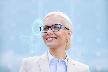 mujer trabajadora: negocios, personas, tecnolog�a y concepto de la educaci�n - joven empresaria sonriente en gafas con pantallas virtuales holograma al aire libre Foto de archivo
