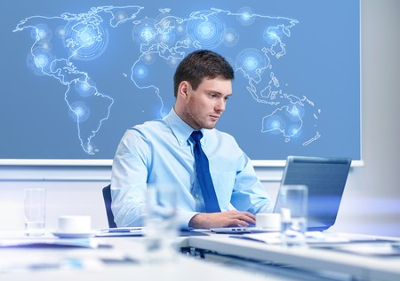 business, people and work concept - businessman with laptop computer and virtual world map sitting in office