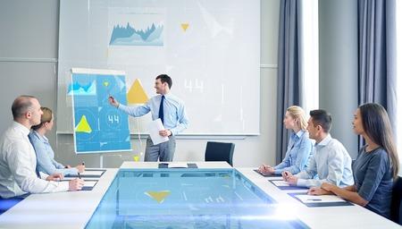 het bedrijfsleven, mensen en teamwork concept - Groep ondernemers met virtuele grafieken projectie bijeenkomst over presentatie in kantoor