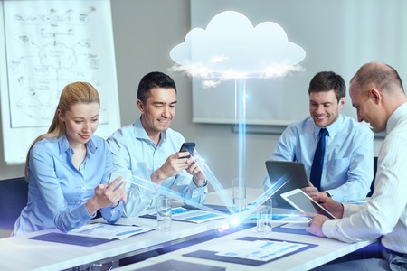 com: business, people, cloud computing and technology concept - smiling business team with smartphones, tablet pc computers working in office