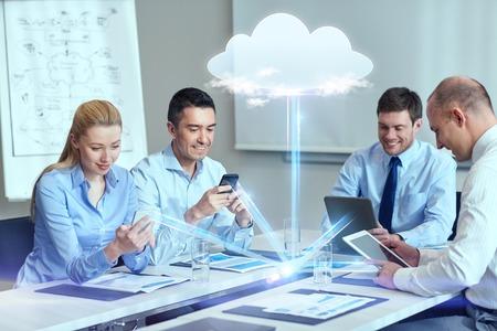 negocio, la gente, el cloud computing y el concepto de tecnología - sonriendo equipo de negocios con los teléfonos inteligentes, computadoras tablet pc trabaja en la oficina