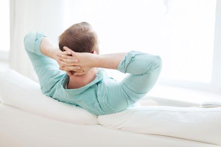 relajado: hogar, ocio, relax y felicidad concepto - hombre tumbado o sentado en el sof� en casa de atr�s