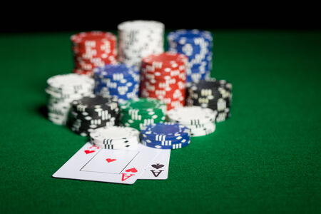 texas hold'em: gambling, fortune, game and entertainment concept - close up of casino chips and playing cards on green table surface