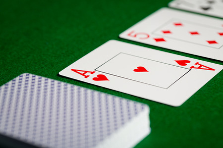hold em: casino, gambling, poker, and entertainment concept - close up of playing cards on green table surface