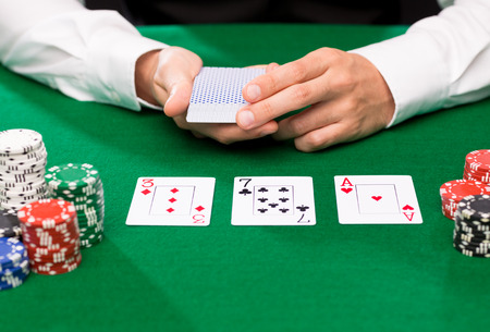 croupier: casino, gambling, poker, people and entertainment concept - close up of holdem dealer with playing cards and chips on green table