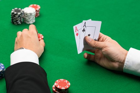casino, gambling, poker, people and entertainment concept - close up of poker player with playing cards and chips at green casino table photo