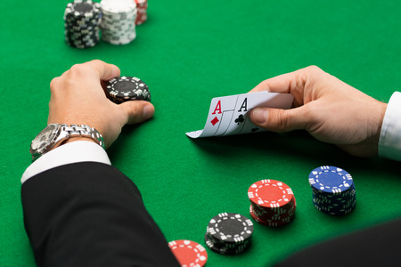 casino dealer: casino, gambling, poker, people and entertainment concept - close up of poker player with playing cards and chips at green casino table
