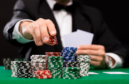 card player: casino, gambling, poker, people and entertainment concept - close up of poker player with playing cards and chips at green casino table