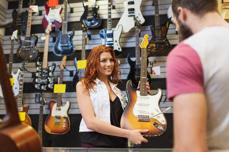 instrumentos musicales: m�sica, venta, gente, instrumentos musicales y concepto de entretenimiento - asistente que muestran la guitarra el�ctrica a los clientes en la tienda de m�sica