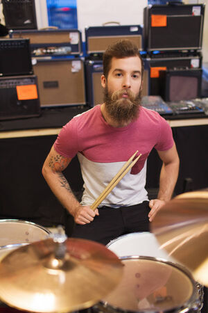 music, sale, people, musical instruments and entertainment concept - male musician playing cymbals at music store photo