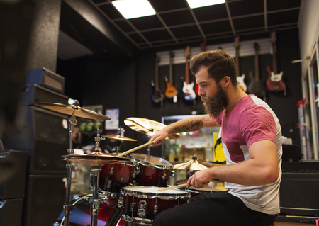 cymbals: music, sale, people, musical instruments and entertainment concept - male musician playing cymbals at music store