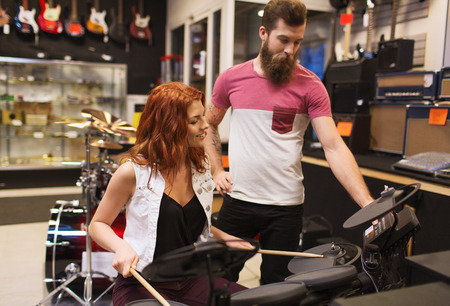 drum kit: music, sale, people, musical instruments and entertainment concept - happy man and woman with drum kit at music store
