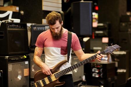 musician: m�sica, venta, gente, instrumentos musicales y concepto de entretenimiento - m�sico masculino o cliente con barba tocando el bajo la guitarra guitarra en la tienda de m�sica
