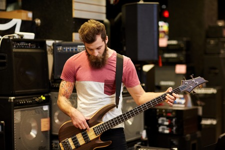 gitara: muzyka, sprzedaż, ludzie, instrumenty muzyczne i rozrywka muzyk koncepcja - mężczyzna z brodą lub klienta gry na gitarze basowej gitarze w sklepie muzycznym