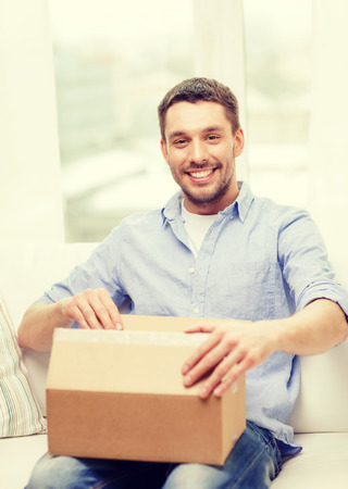 recieve: post, home and lifestyle concept - smiling man with cardboard boxes at home