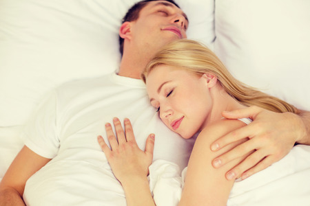 hotel, travel, relationships, and happiness concept - happy couple sleeping in bed photo