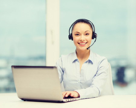 business, communication and call center concept - friendly female helpline operator with headphones and laptop computer photo